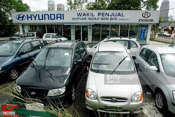 Unsold imported cars sit in a dealer's lot in Kuala Lumpur 28 January 2004 Malaysia's vehicle sales fell for the first time in five years in 2003 as...