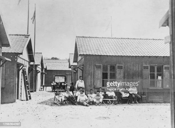 Unspecified athletes sitting in front of a cabin in the Olympic Village at the 1924 Summer Olympics in Paris, France, 1924. The 1924 Games were the...