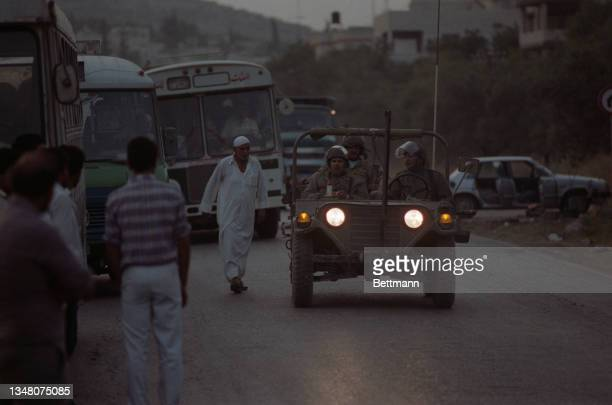 Unspecified military personnel riding in a Jeep pass buses and Middle Eastern people as night falls over an unspecified area of the West Bank, 1988.