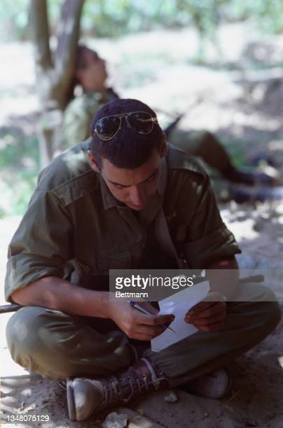Unspecified military personnel taking a break, sitting cross legged, reading from a sheet of paper, a pen in his hand, in an unspecified area of the...