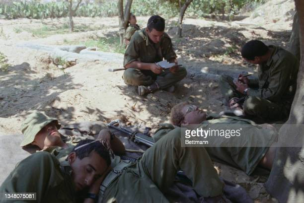 Unspecified military personnel taking a break, some lying on the ground other sit cross legged, reading from a sheet of paper, a pen in his hand, as...
