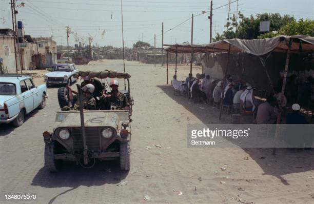 Unspecified military personnel wearing helmets with visors driving a Jeep alongside a covered cafe at the roadside in an unspecified area of the West...