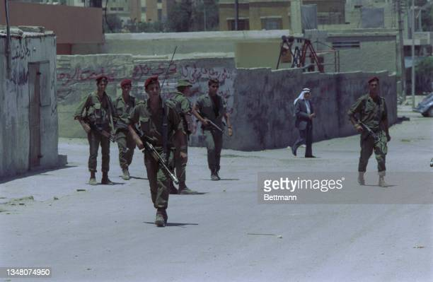 Unspecified military personnel wearing military fatigues and a red berets, armed with assault rifles, patrolling an unspecified area of the West...