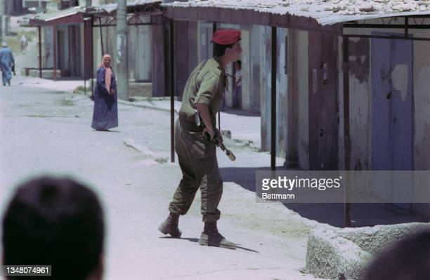 Unspecified military personnel wearing military fatigues and a red beret, armed with an assault rifle, with people on the street outside a property...