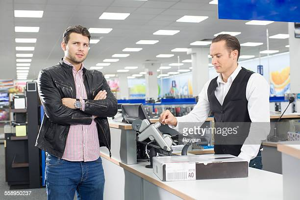 unsure shopper paying with credit card in electronics store - electronics store stock photos and pictures