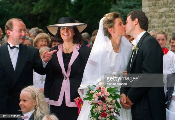 Unter den freundlichen Blicken der Brauteltern gibt sich das Brautpaar nach der kirchlichen Trauung einen Hochzeitskuß Die deutsche...