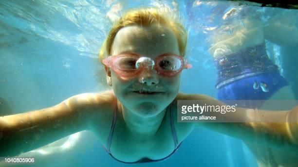 Unter Wasser schaut die neunjährige Merle am im Freibad der Kokerei Zeche Zollverein in Essen durch eine Glasscheibe. Bei mehr als 35 Grad im...