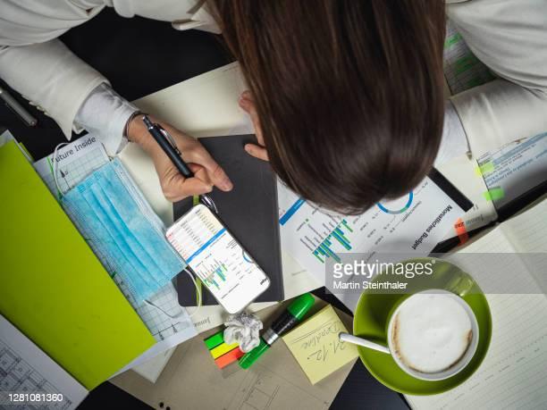 unternehmer frau bei einnahmen - ausgaben rechnung in der covid-19 situation - frau fotografías e imágenes de stock