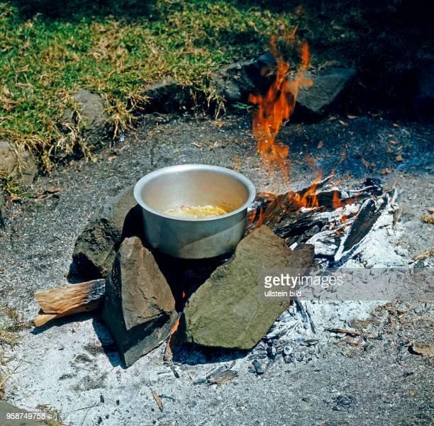 Unterwegs auf Safari in outdoor rustikale Feuerstelle mit holzbeheizter Kochschuessel auf dafuer vorgesehenem Platz in der Wildnis