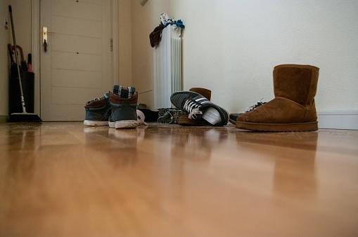 Untidy hallway with hardwood floor and plenty of shoes 931413684