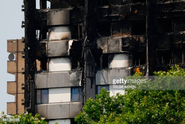 Untouched cladding on the lower floors is seen on the burnt out shell of the Grenfell Tower block in North Kensington west London on June 18 2017 The...