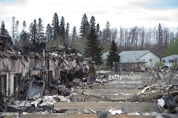 Untouched homes are seen in the background as others destroyed by fire are seen in the foreground in the Abasands neighbourhood during a media tour...