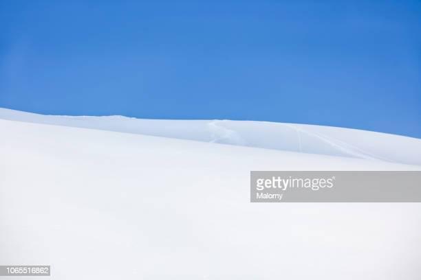 untouched ski run with pristine snow and blue sky. - 深い雪 ストックフォトと画像
