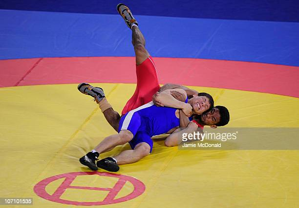 Unurbat Purevjav of Mongolia grapples with Chung Song Yang of Peoples Republic of Korea in the Men's Freestyle 66kg class at Huagong Gymnasium during...