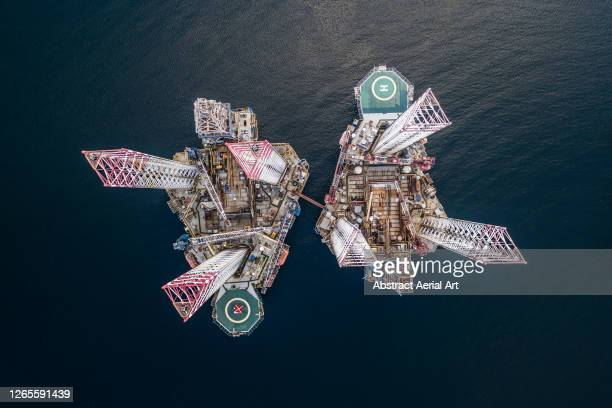 unusual aerial perspective showing two connected oil rigs in an ocean channel, cromarty firth, scotland, united kingdom - contemplation stock pictures, royalty-free photos & images