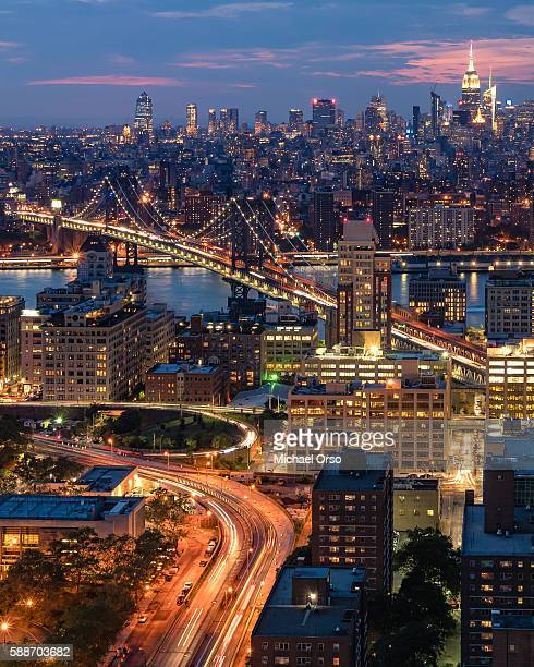 unusual bird's eye view, aerial image of Manhattan Bridge, Manhattan NYC skyline, East River during blue hour. After sunset, early evening. Viewed from a rooftop in Downtown Brooklyn.
