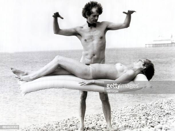 Unusual Magician Paul Matthews and assistant Michele Dawson practising a trick on Brighton's Nudist Beach 2nd May 1984
