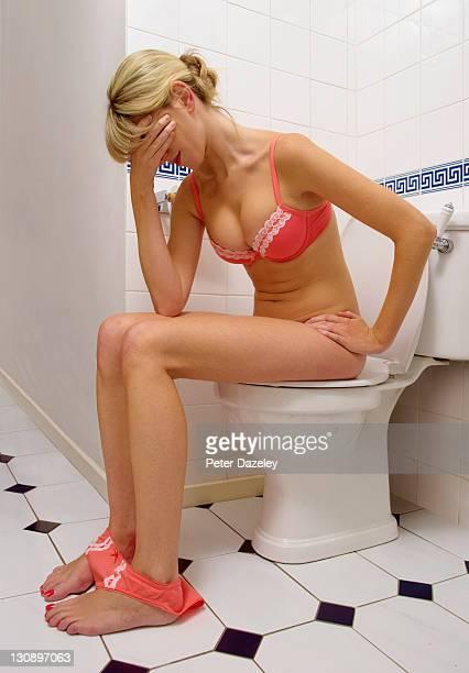 unwell girl on toilet - hemorroida imagens e fotografias de stock