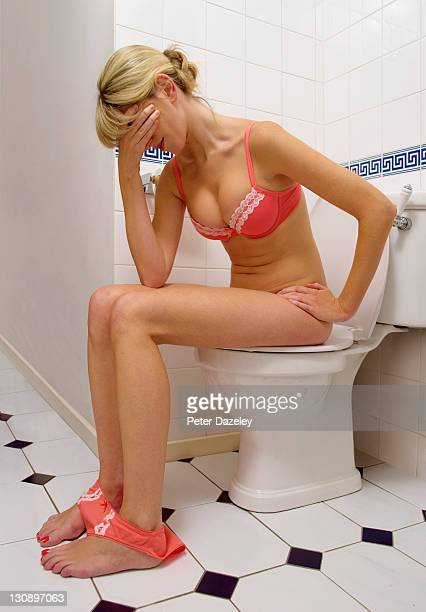 unwell girl on toilet - emorroidi foto e immagini stock