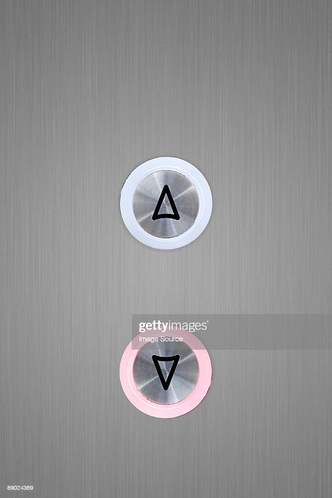 Up and down elevator buttons with down button lit up : Stock Photo