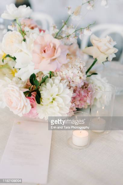 up close image of a table setting at a wedding reception with flower arrangement and candles lit - mazzo di rose foto e immagini stock
