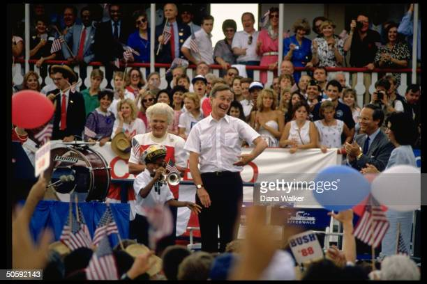 Upbeat pres cand Barbara Bush serenaded by band framed by supporters at Riverwalk campaign rally during Repub Natl Convention