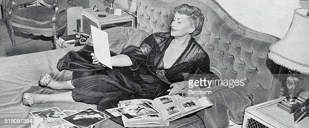 Updating her scrapbook while lying in bed is Mama Jolie Gabor the mother of Zsa Zsa Eva and Magda the famous Gabor sisters