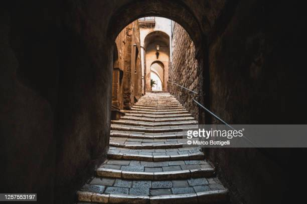 uphill alley with stairs in an old turf village, italy - villaggio foto e immagini stock