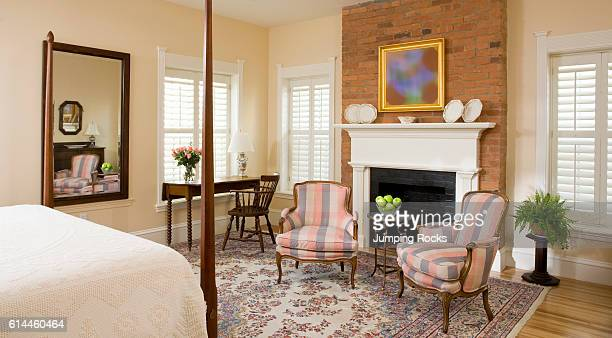 Upholstered Armchairs In Front Of Fireplace At Foot Four Poster Bed