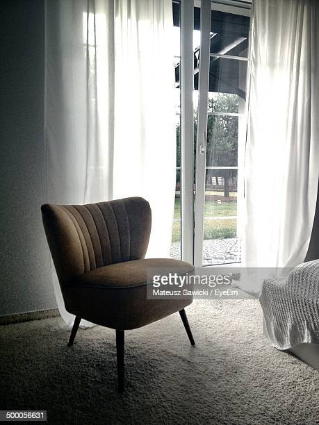 Upholstered chair in front of closed glass doors
