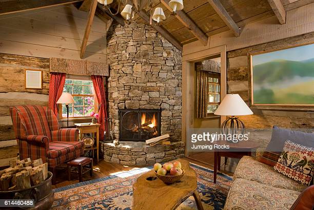 Upholstered chair next to rustic stone fireplace with lit fire