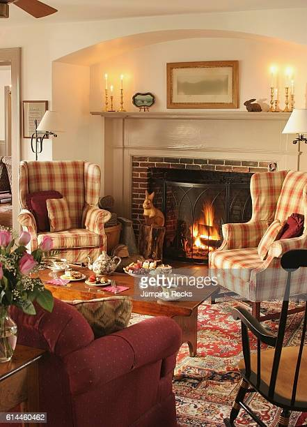 Upholstered furniture arranged around coffee table in front of fireplace with lit fire, Rabbit Hill Inn, Vermont, USA.