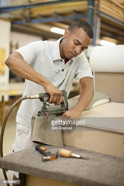 Upholsterer attaching textile to frame using staple gun