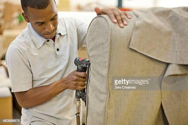 Upholsterer attaching textile to sofa using staple gun