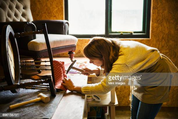 Upholstery workshop. A woman hammering fabric and padding to a chair frame.