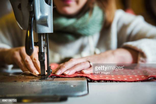 Upholstery workshop. A woman seated working with an industrial sewing machine, stitching fabric.
