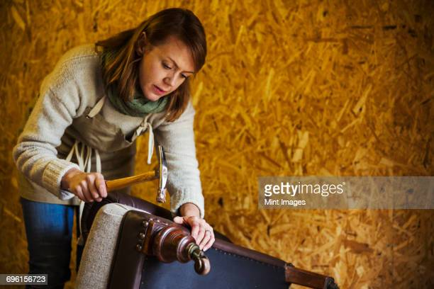 Upholstery workshop. An upholsterer using a hammer to secure fabric and padding to a chair leg.