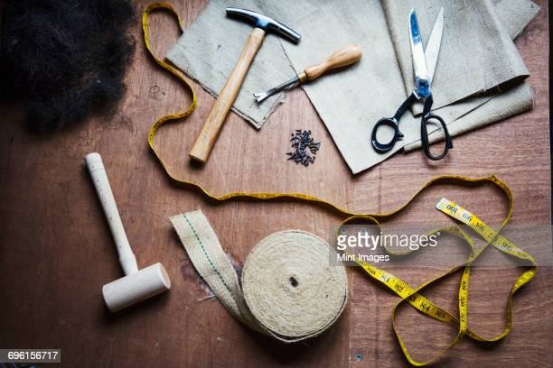Upholstery workshop. Overhead view of hand tools, hammer, tape, tape measure and scissors.