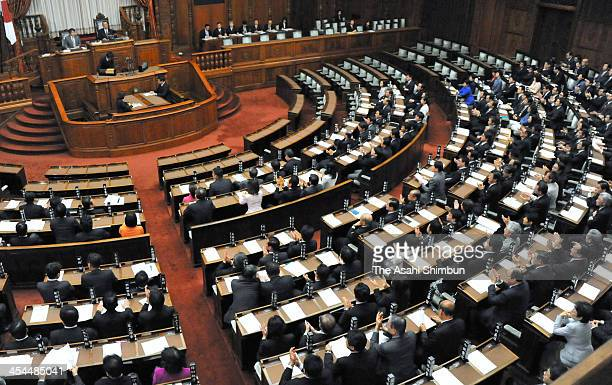 Upper House members of the ruling coalition applaud as the state secrets protection law is enacted at the diet building on December 6 2013 in Tokyo...