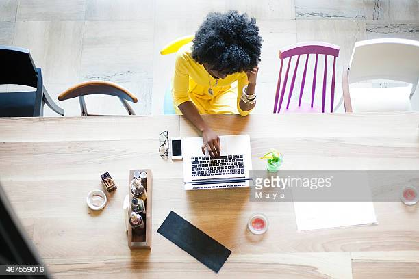 Upper view of woman sitting on a table using a laptop