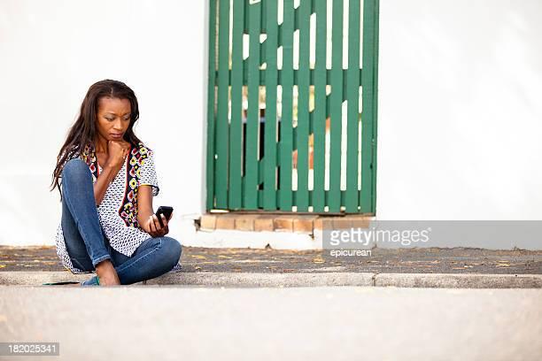 Femme africaine en colère à envoyer des SMS sur un trottoir