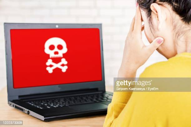 upset asian business woman with computer screen showing virus warning alert, hacking,piracy concept - e mail spam stock pictures, royalty-free photos & images