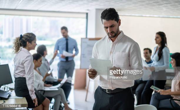 upset businessman at the office reading a document - hispanolistic stock photos and pictures