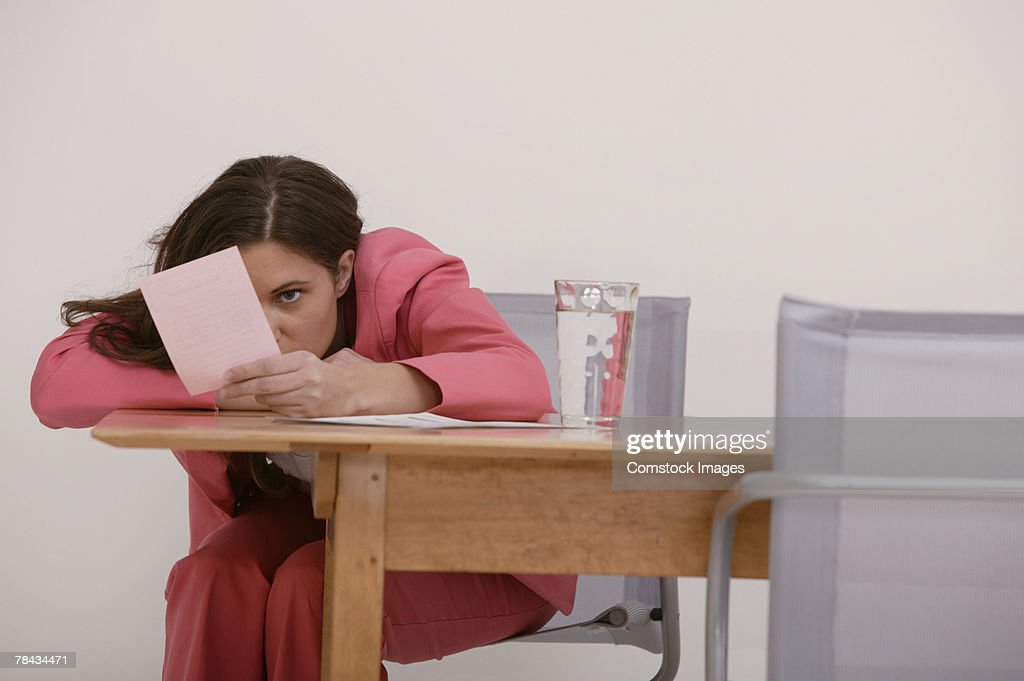 Upset businesswoman staring at pink slip : Stockfoto
