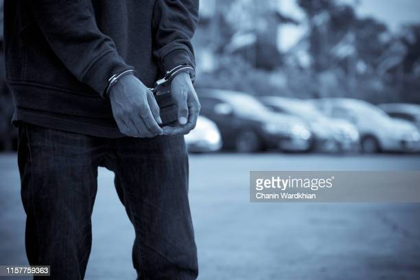 upset handcuffed man imprisoned for financial crime, punished for serious fraud - arrest stock pictures, royalty-free photos & images