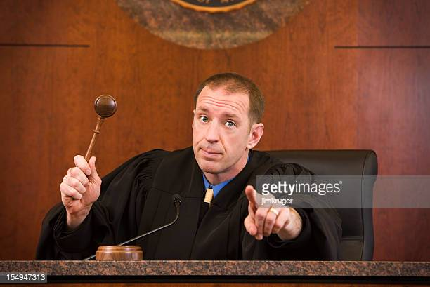Upset judge swinging gavel and pointing