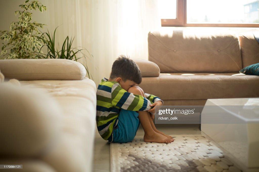 Upset little boy sitting on the floor : Stock Photo