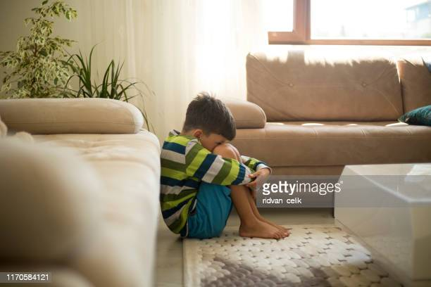 upset little boy sitting on the floor - caught in the act stock pictures, royalty-free photos & images