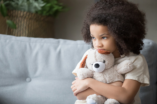 Upset lonely african kid girl holding teddy bear looking away 1135353604