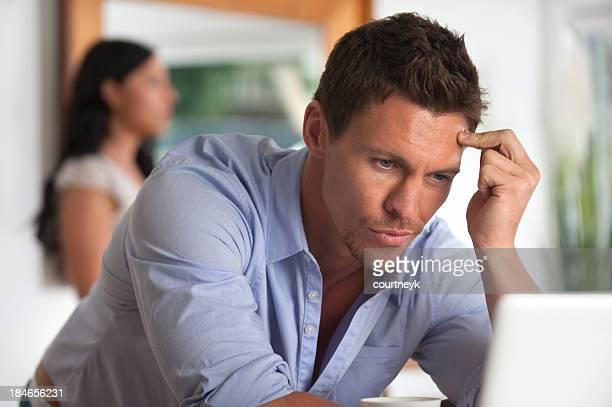 Upset man looking at a computer screen